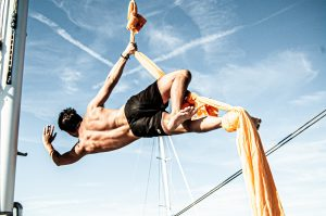 man in black tank top and yellow shorts holding rope