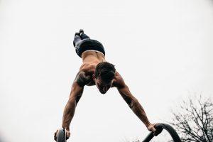 topless man doing hand stand on metal bars